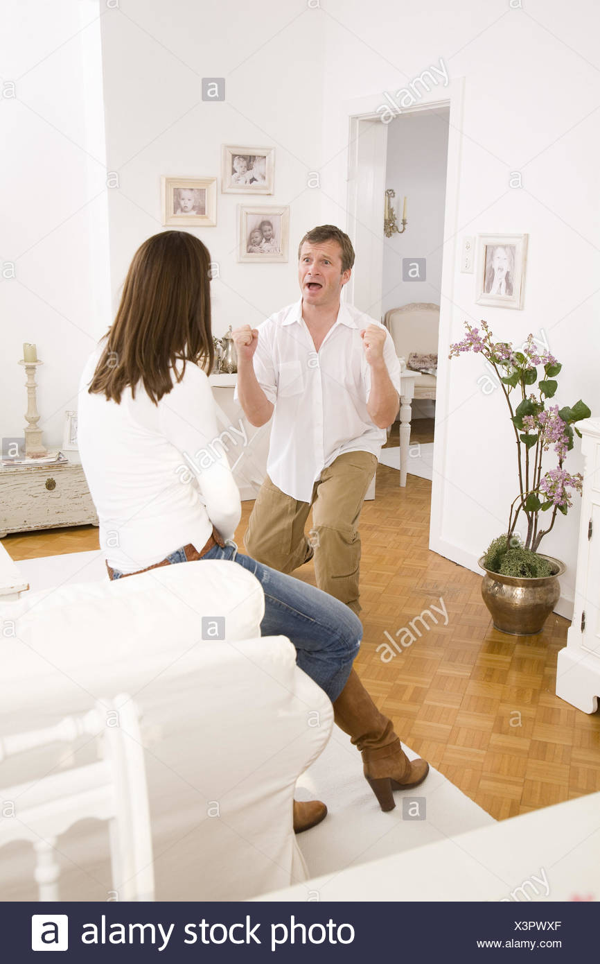Living rooms, pair, woman, back-opinion, man, gesture, jubilation, apartment, people, 40-50 years, two, happily, contentedly, screams, kneels down, enthusiasm, joy, relief, partnership, harmony, love, solidarity, affection, at home, interior, - Stock Image