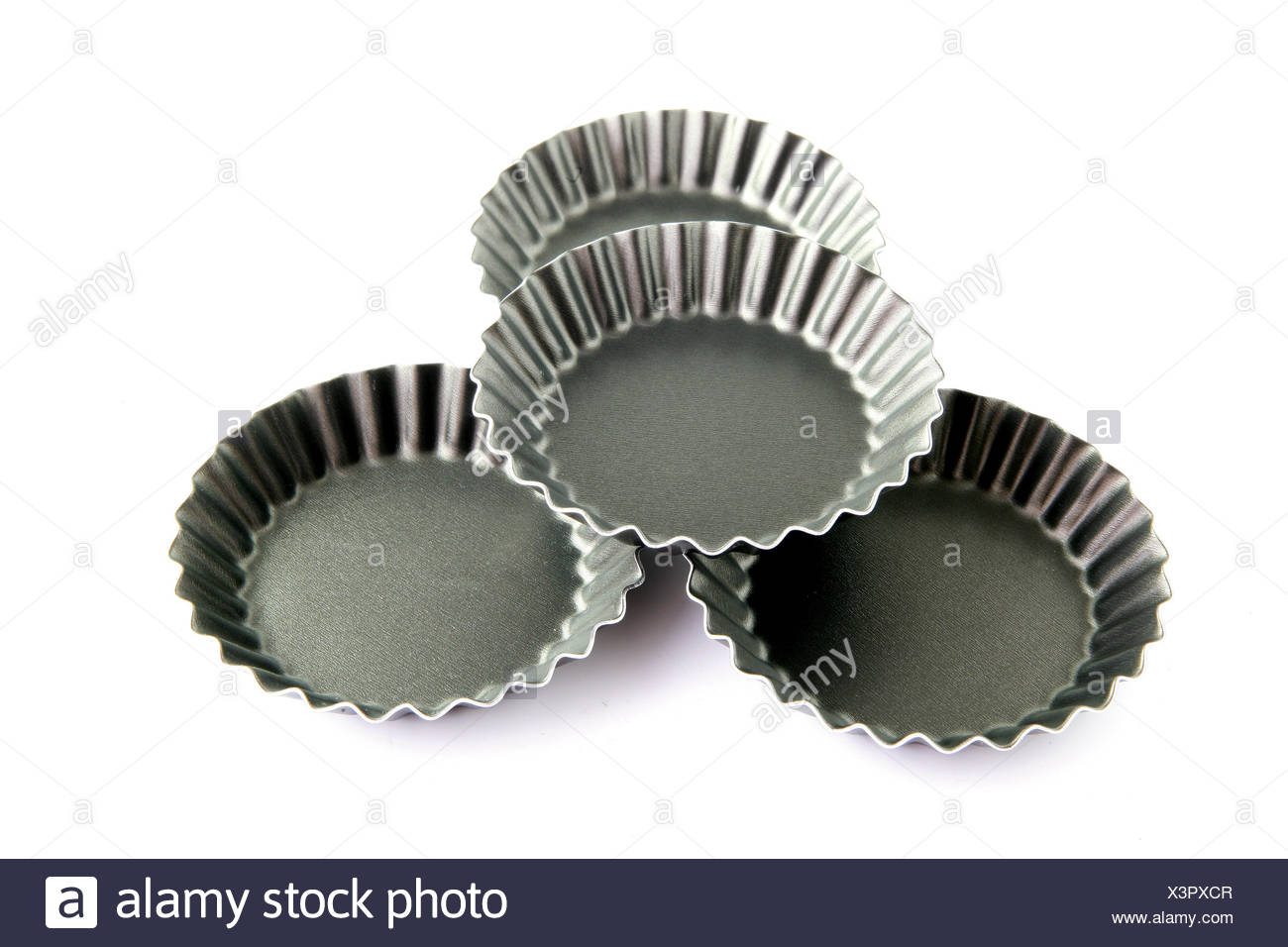 objects four horizontal cake pie 4 molds custard kitchen accessories white - Stock Image