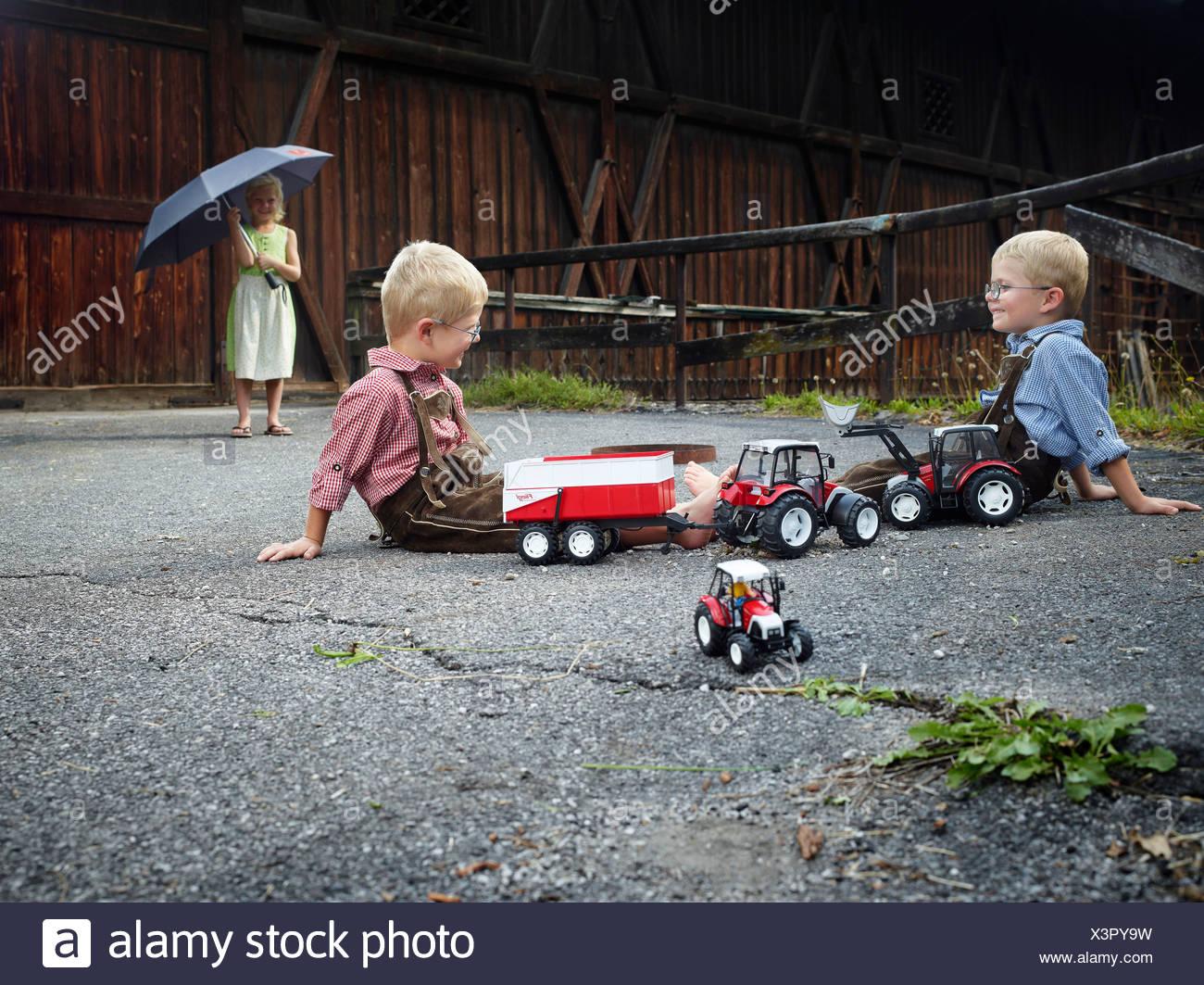 Children playing with toy tractors on farm, Reith im Alpbachtal, Kufstein District, North Tirol, Tirol, Austria - Stock Image