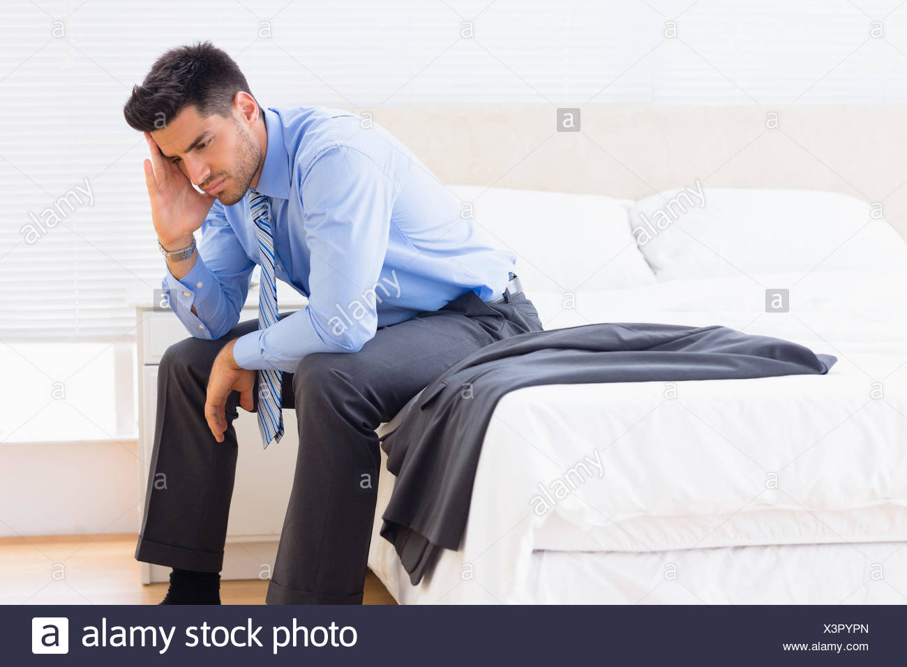 Frowning businessman sitting at edge of bed - Stock Image