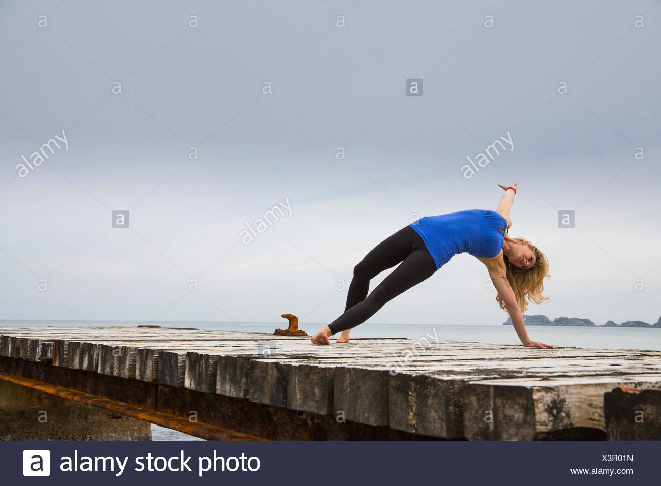Mid adult woman practicing yoga move on wooden sea pier - Stock Image