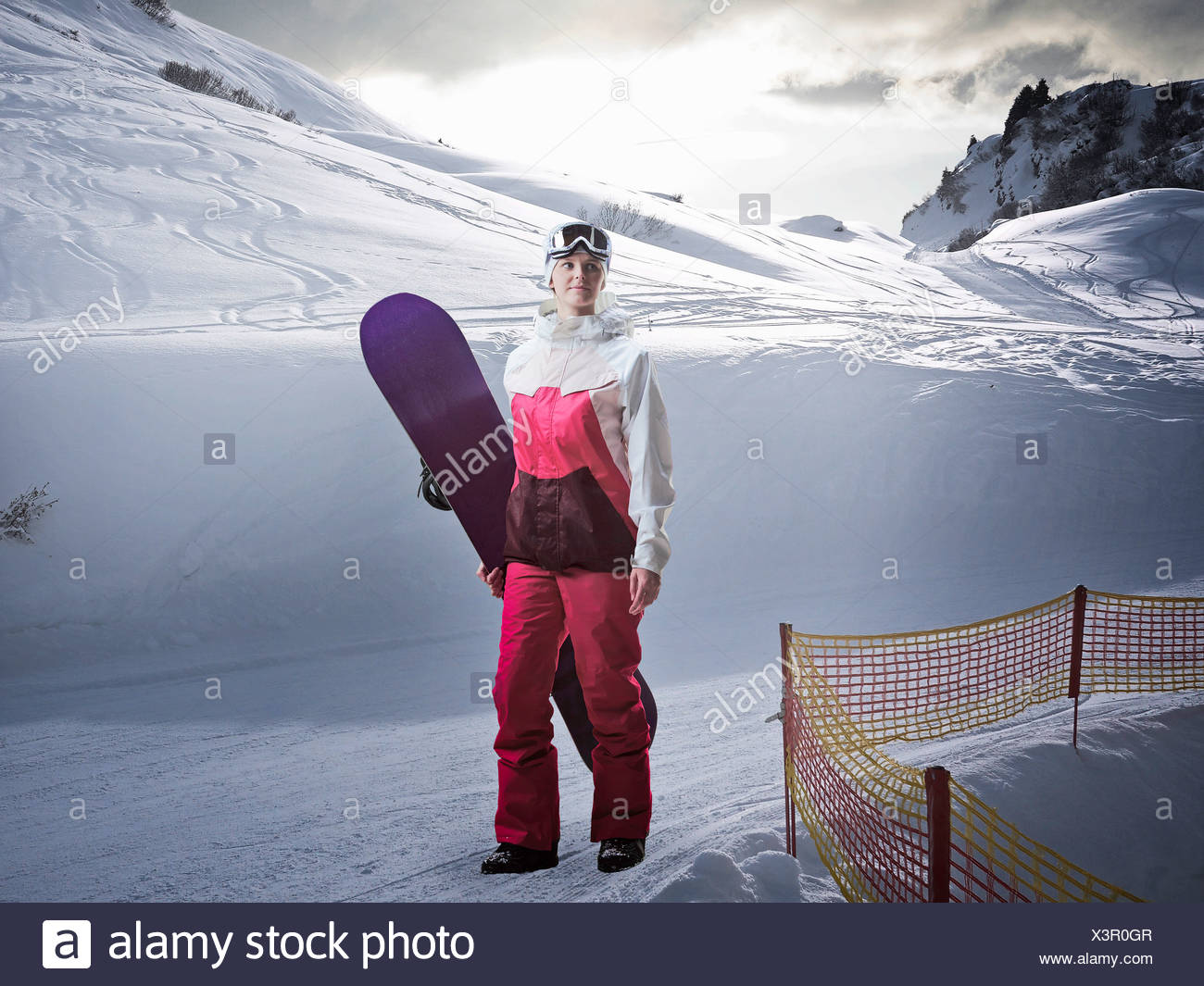 Woman carrying snowboard on snowy slope - Stock Image