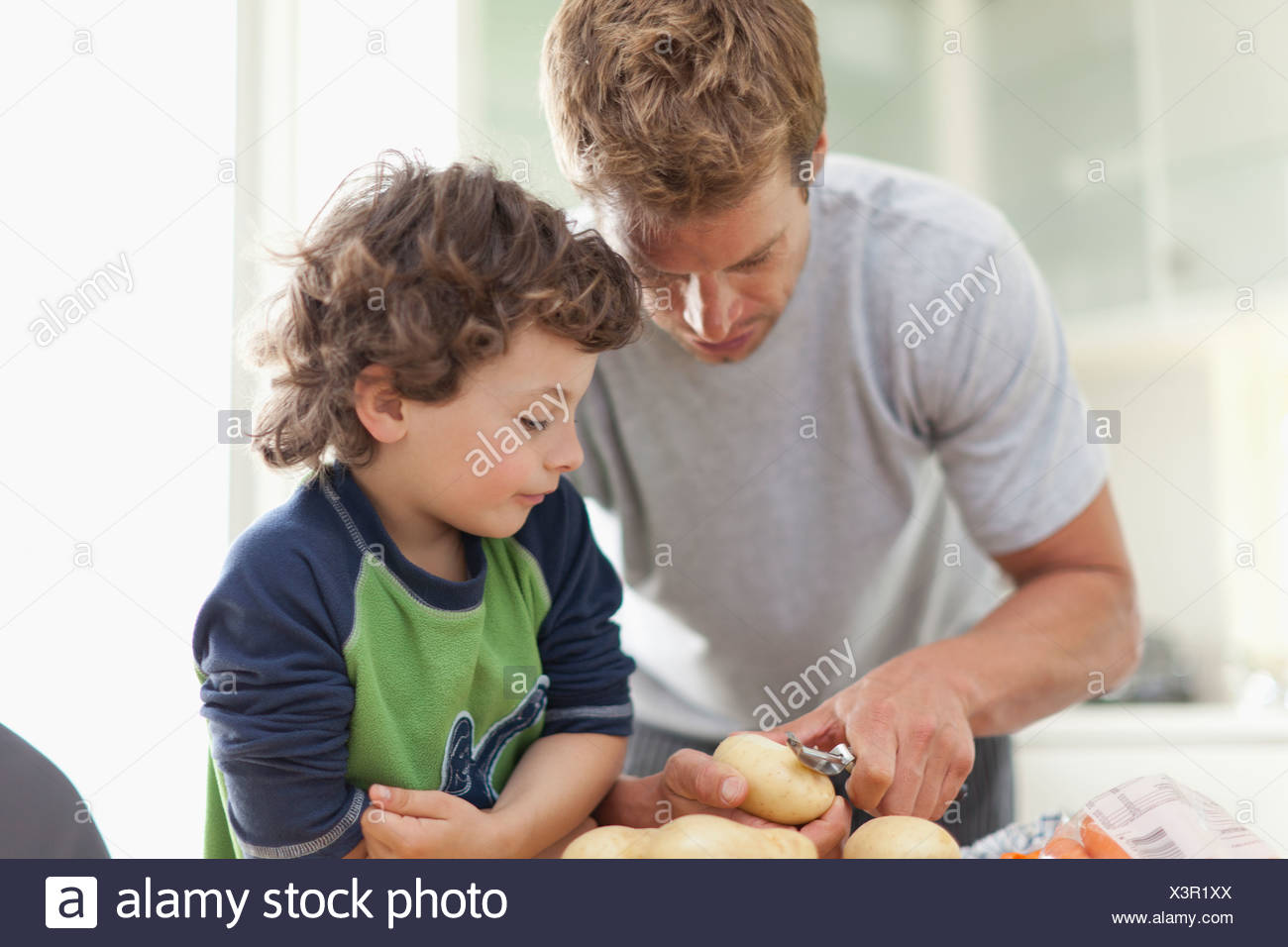 Father helping son peel potatoes - Stock Image