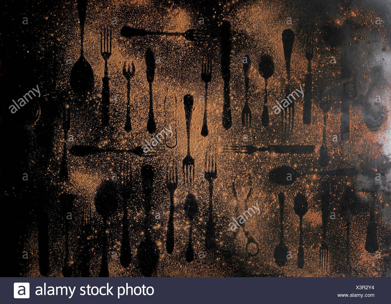 Shapes of disappeared vintage cutlery on brown dust over black metal background. Top view - Stock Image