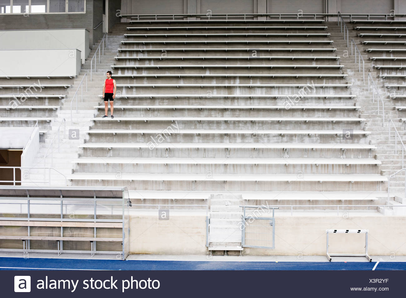 Man standing on stadium steps - Stock Image