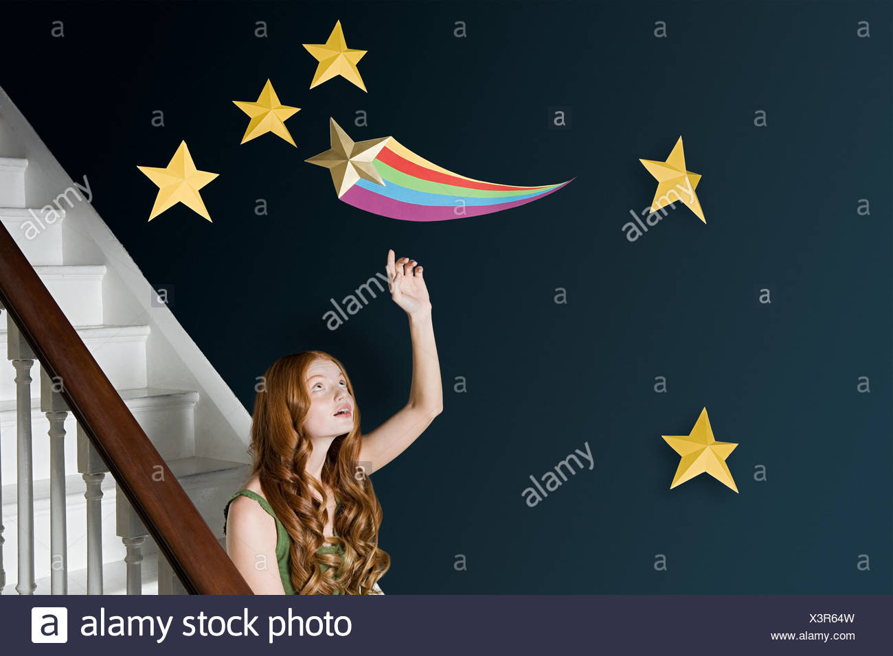 A woman reaching for a shooting star - Stock Image