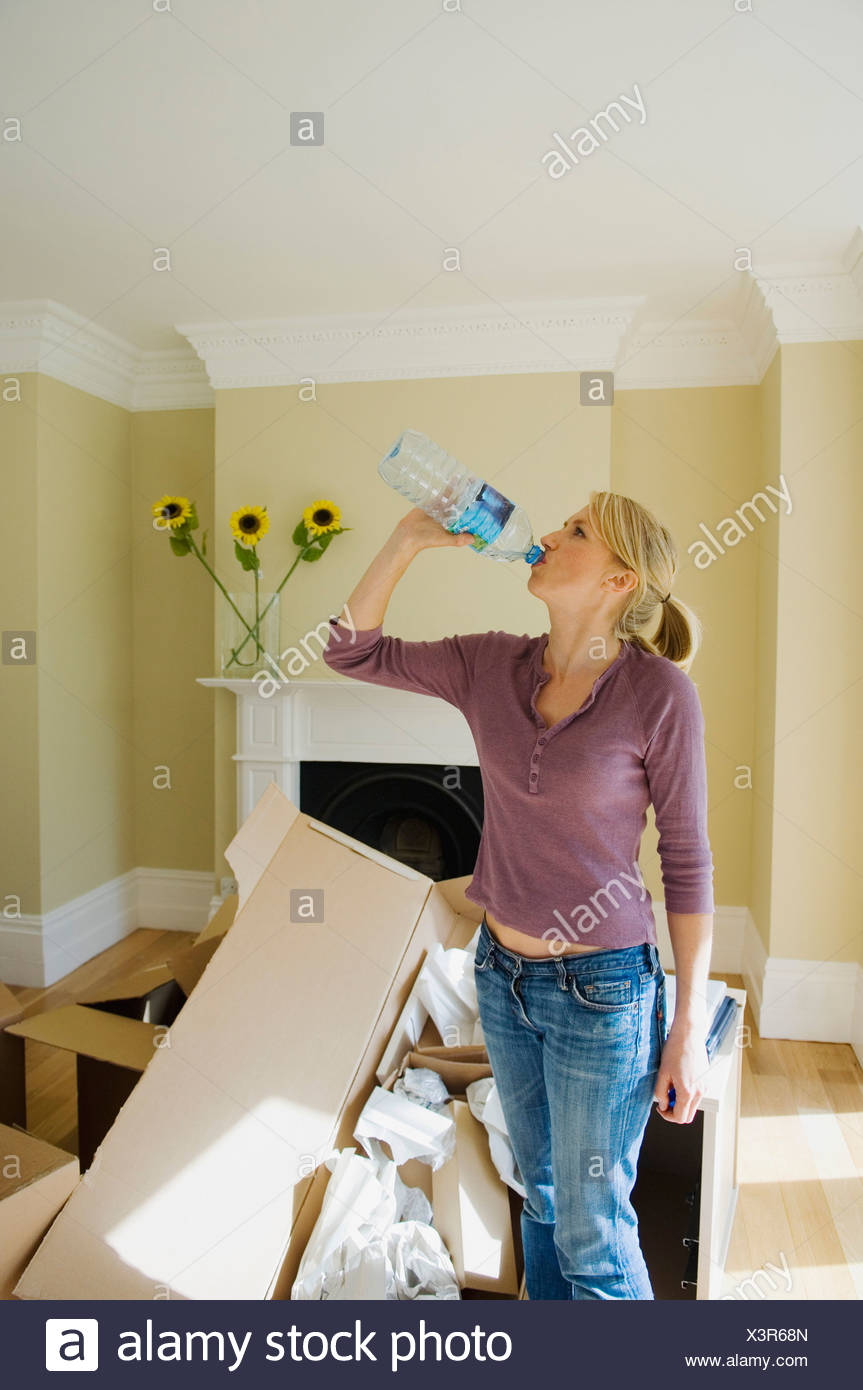 Woman drinking water in new home - Stock Image