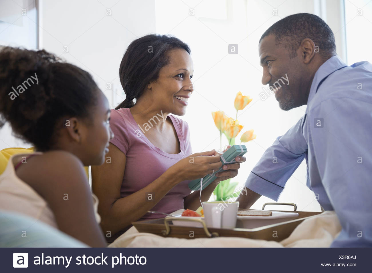 Woman opening birthday gift in bedroom - Stock Image