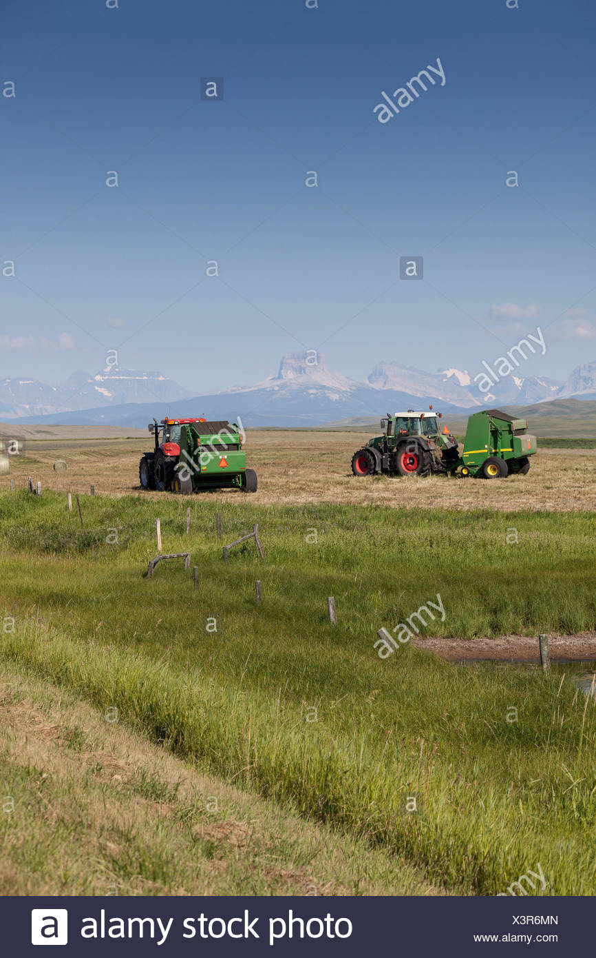 Tractors and hay balers on a farm with a mountain backdrop