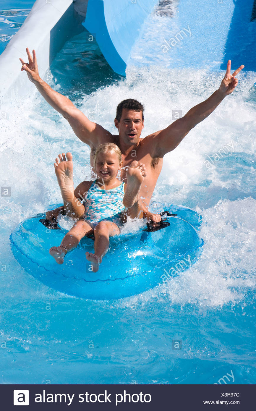 Father and daughter sliding down waterslide on innertube in water park Stock Photo