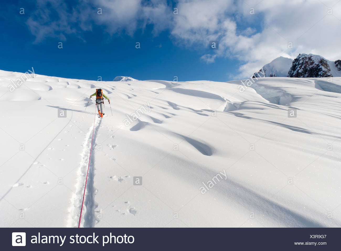 Skier breaks trail and leads rope team to climb Mount Torbert, Tordrillo Mountains in Southcentral Alaska - Stock Image