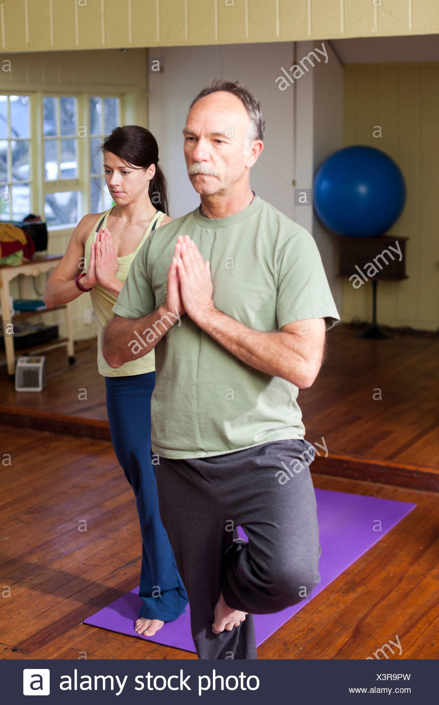 An older man in front of a younger woman practices a yoga position in a small studio. - Stock Image