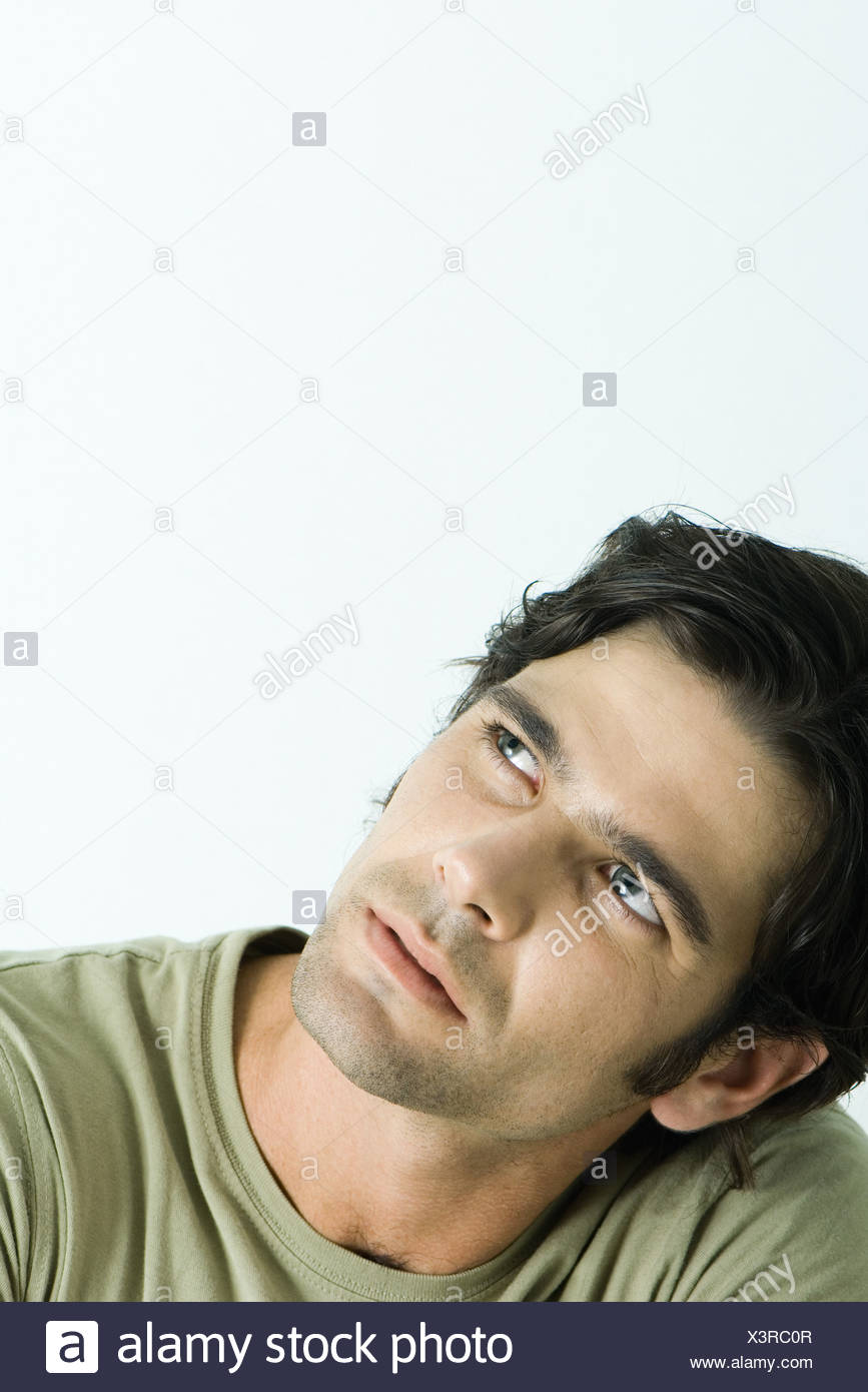 Man tilting head and looking up, head and shoulders, portrait - Stock Image