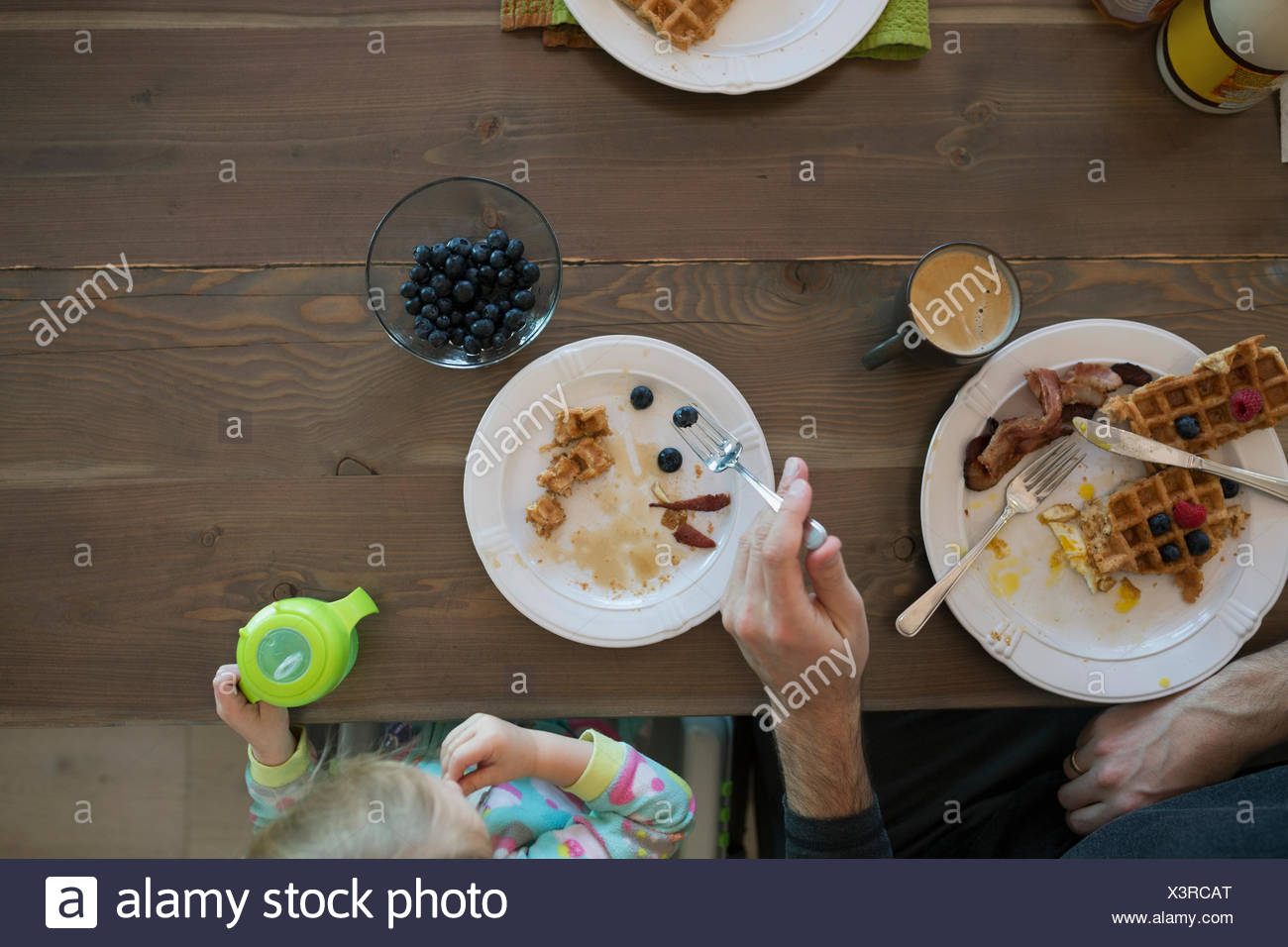 Overhead father and daughter eating waffles breakfast table - Stock Image
