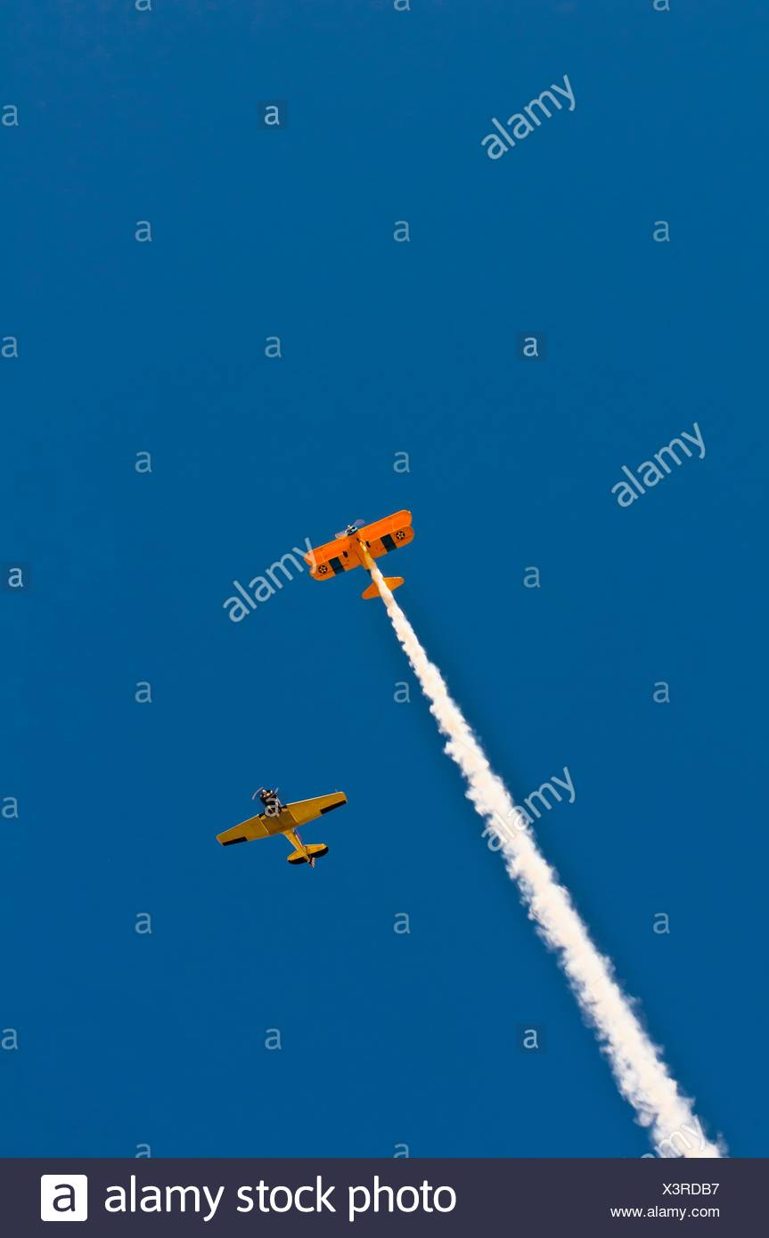 Biplane with smoke trail flying over the Western Welcome Week parade in downtown, Littleton, Colorado USA - Stock Image