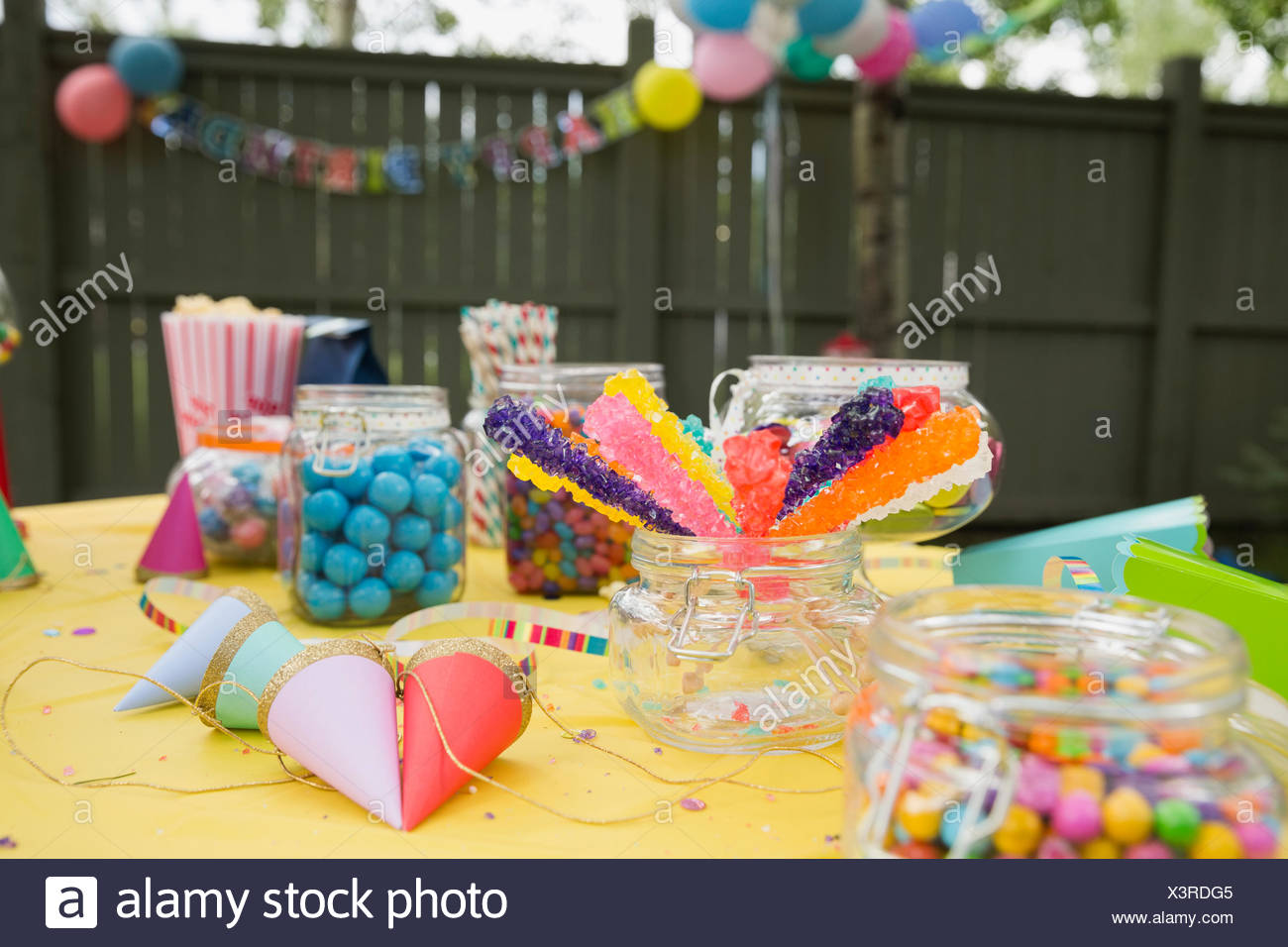 Candy party hats on birthday party table backyard - Stock Image