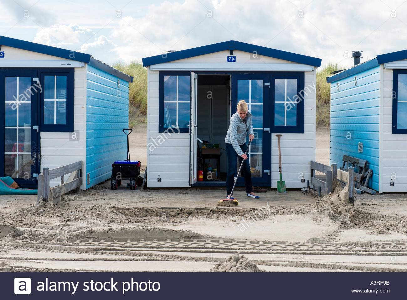 Hook of Holland, Netherlands. Mature adult woman sweeping the front yard of her little beach house free of sand. - Stock Image
