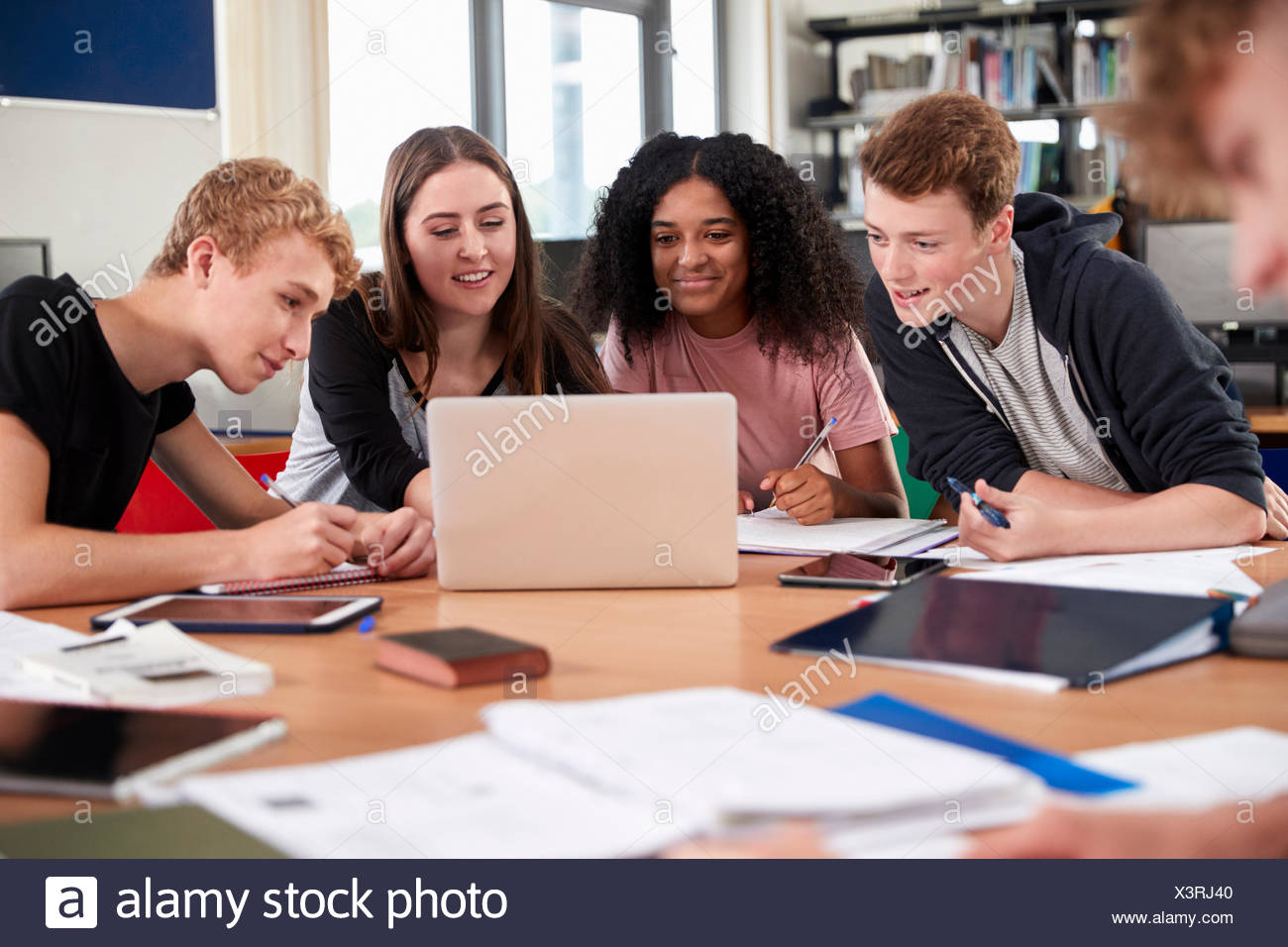 Group Of College Students Collaborating On Project In Library - Stock Image