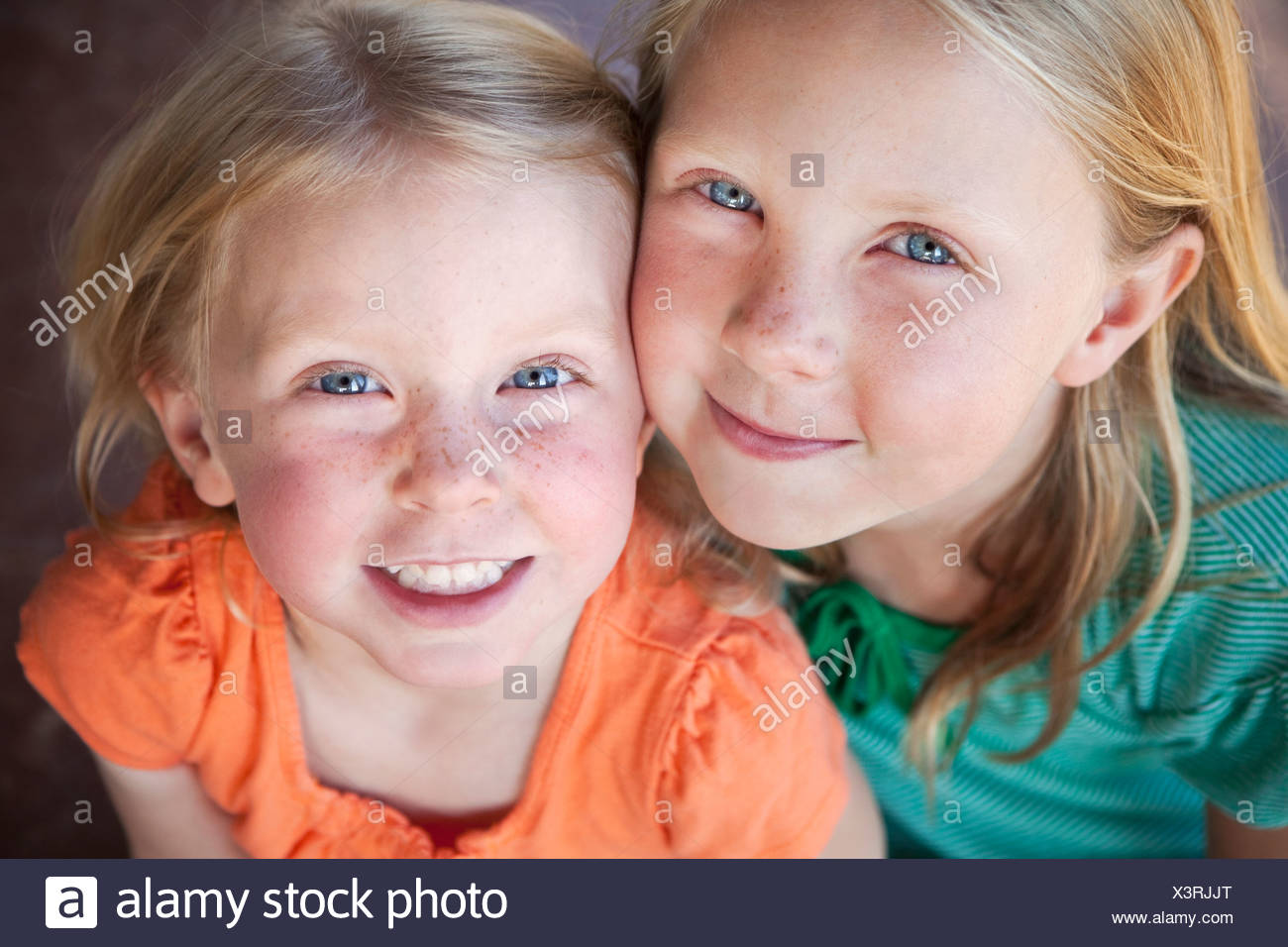A portrait of two sisters smiling. Two young girls, with blue eyes and blonde hair. - Stock Image