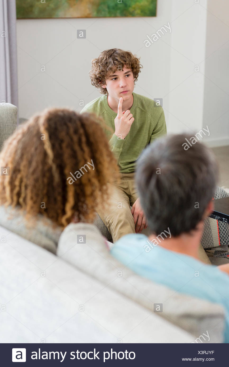 Family sitting in a living room at home - Stock Image