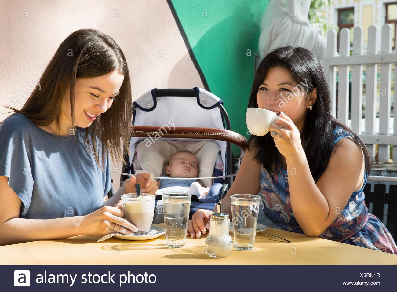 Young woman with mother and baby daughter drinking coffee at sidewalk cafe - Stock Image