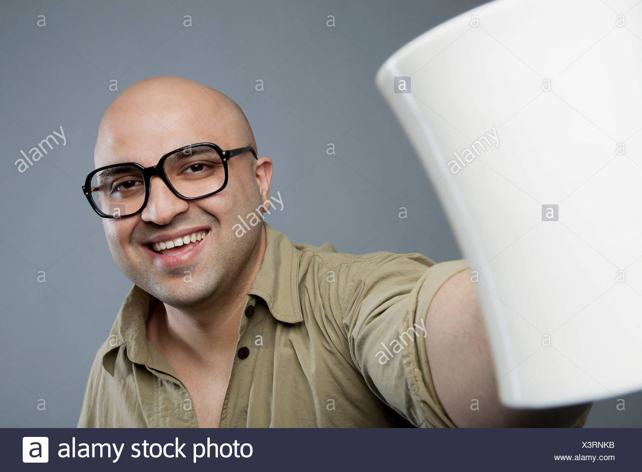 Bald man with a mug of tea - Stock Image