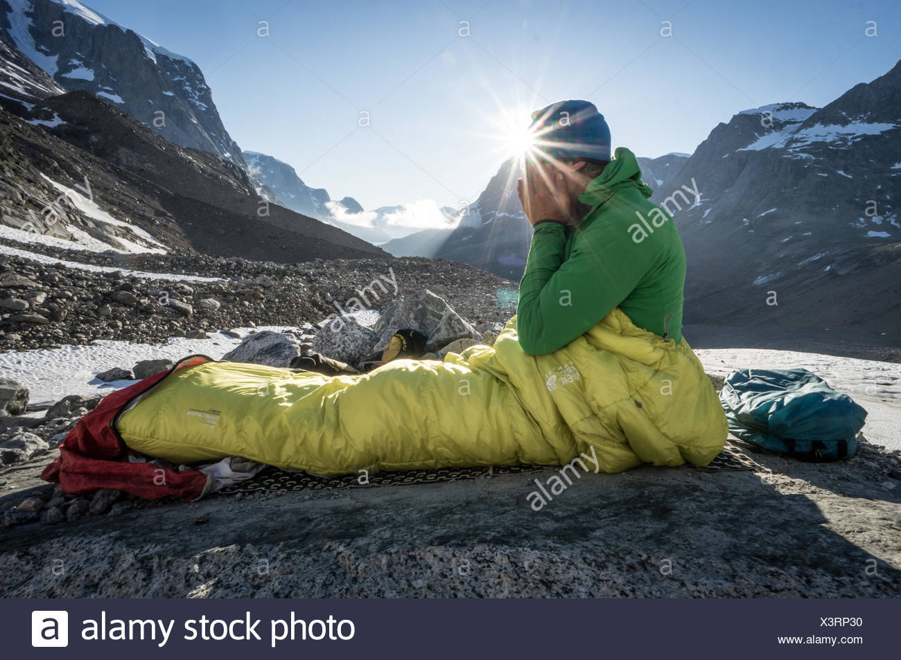 Male hiker waking from a restful sleep in the Skjoldungen range, Greenland. - Stock Image