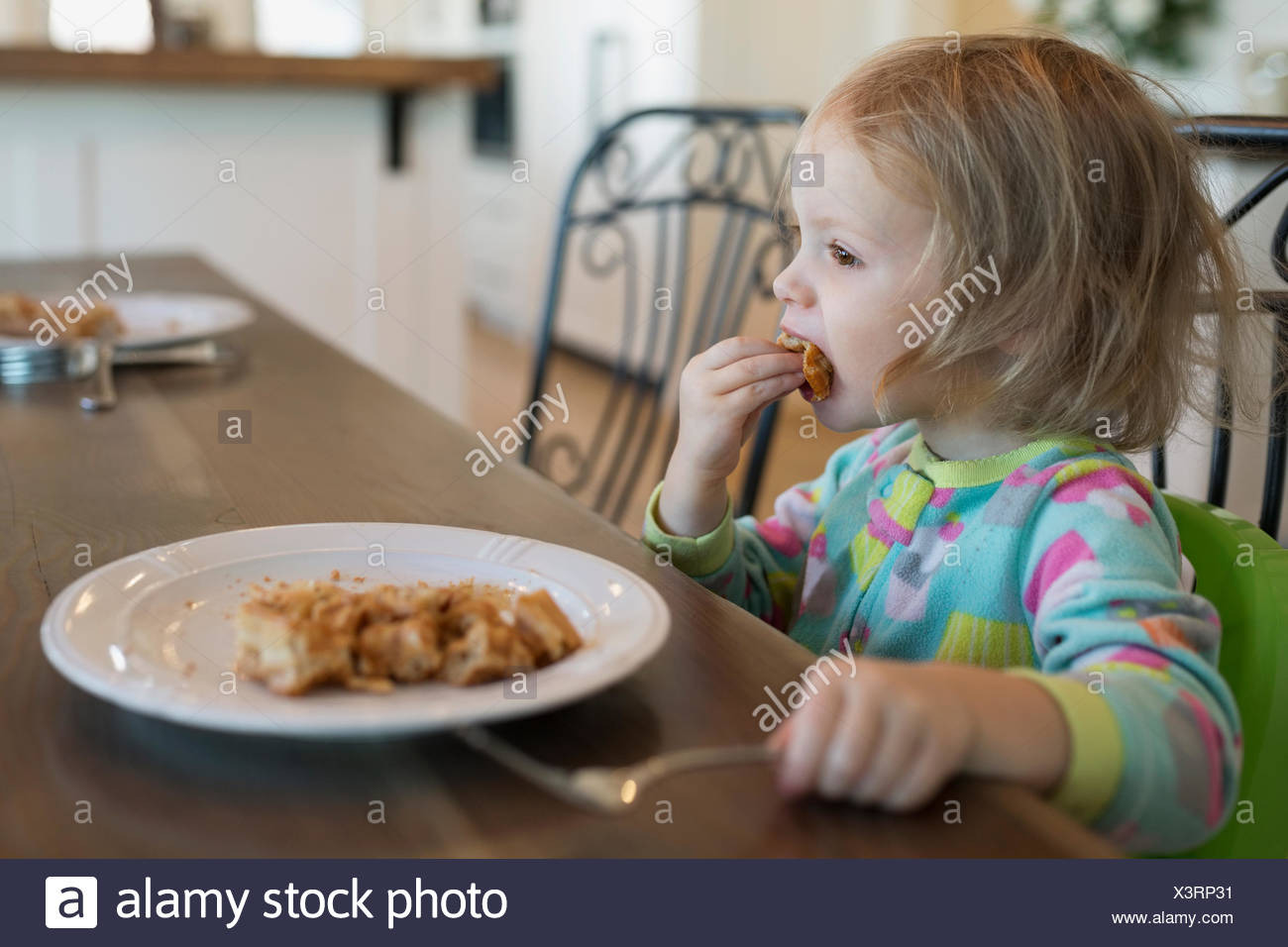 Girl eating waffles at breakfast table - Stock Image