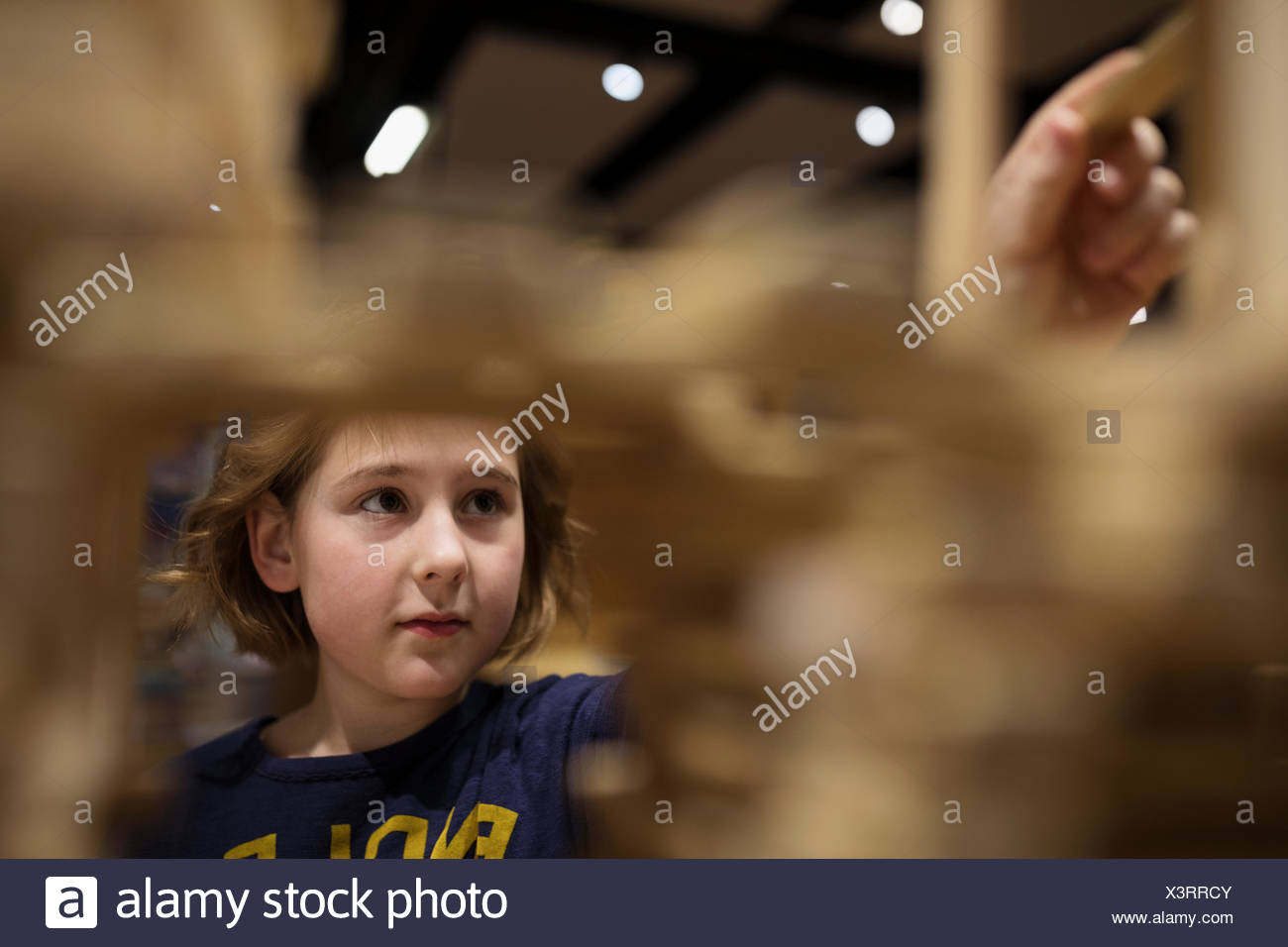 Curious girl reaching peg in science center - Stock Image