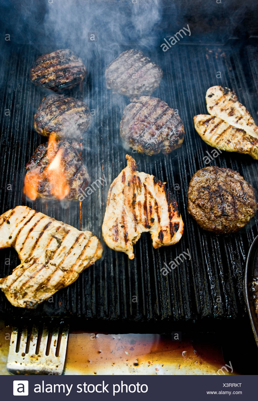 Meat cooking on grill - Stock Image