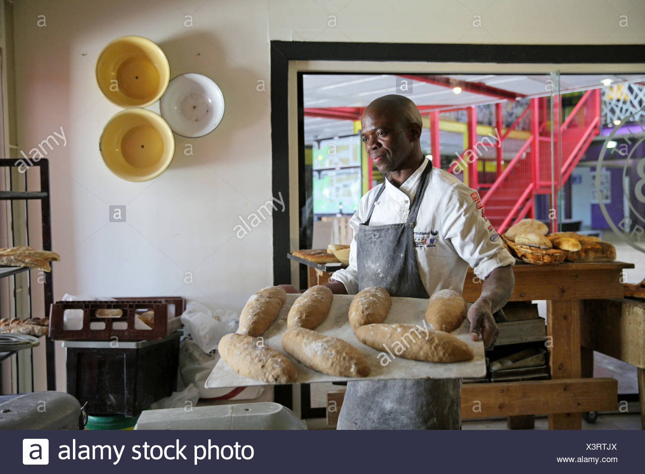 African baker carrying tray of loaves of bread in bakery - Stock Image