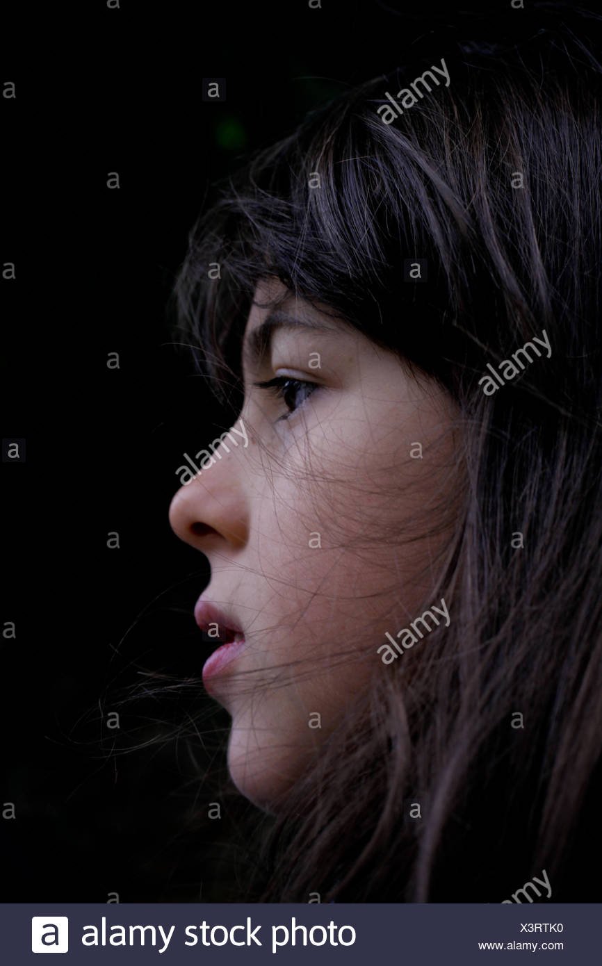 Profile view of girl (6-7) on black background - Stock Image