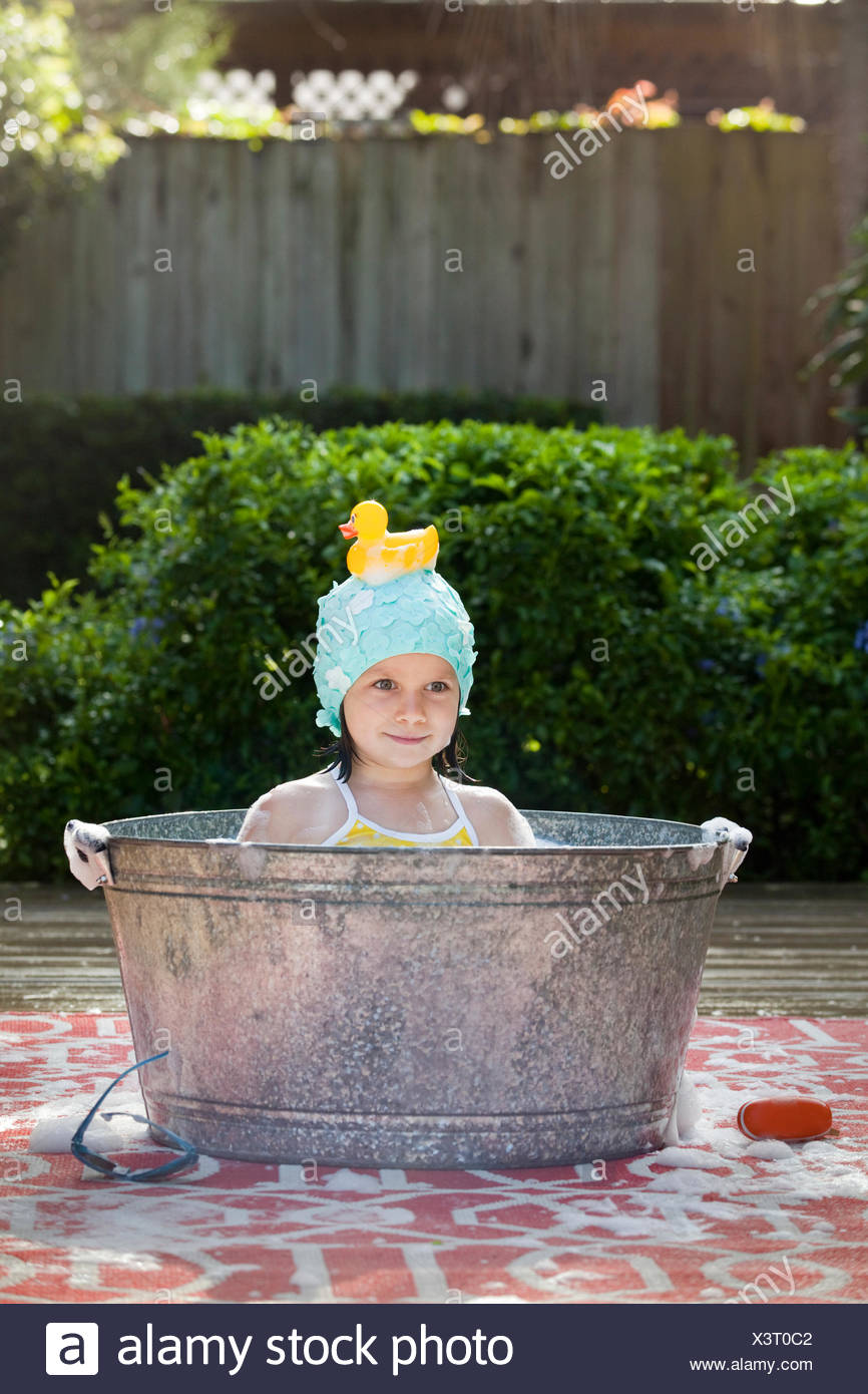 Portrait of girl in bubble bath in garden with rubber duck on head - Stock Image