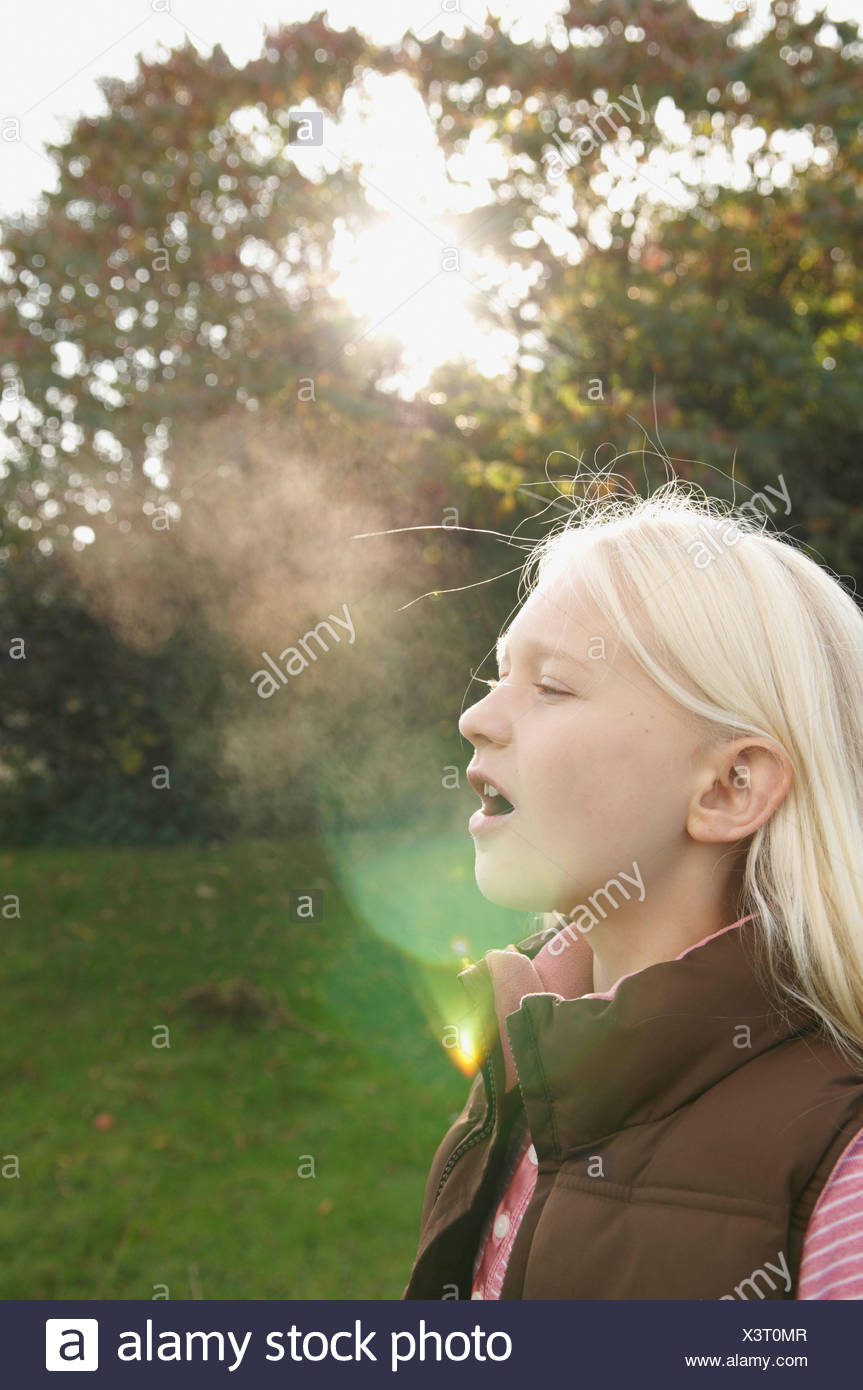 Girl breathing into cold air - Stock Image