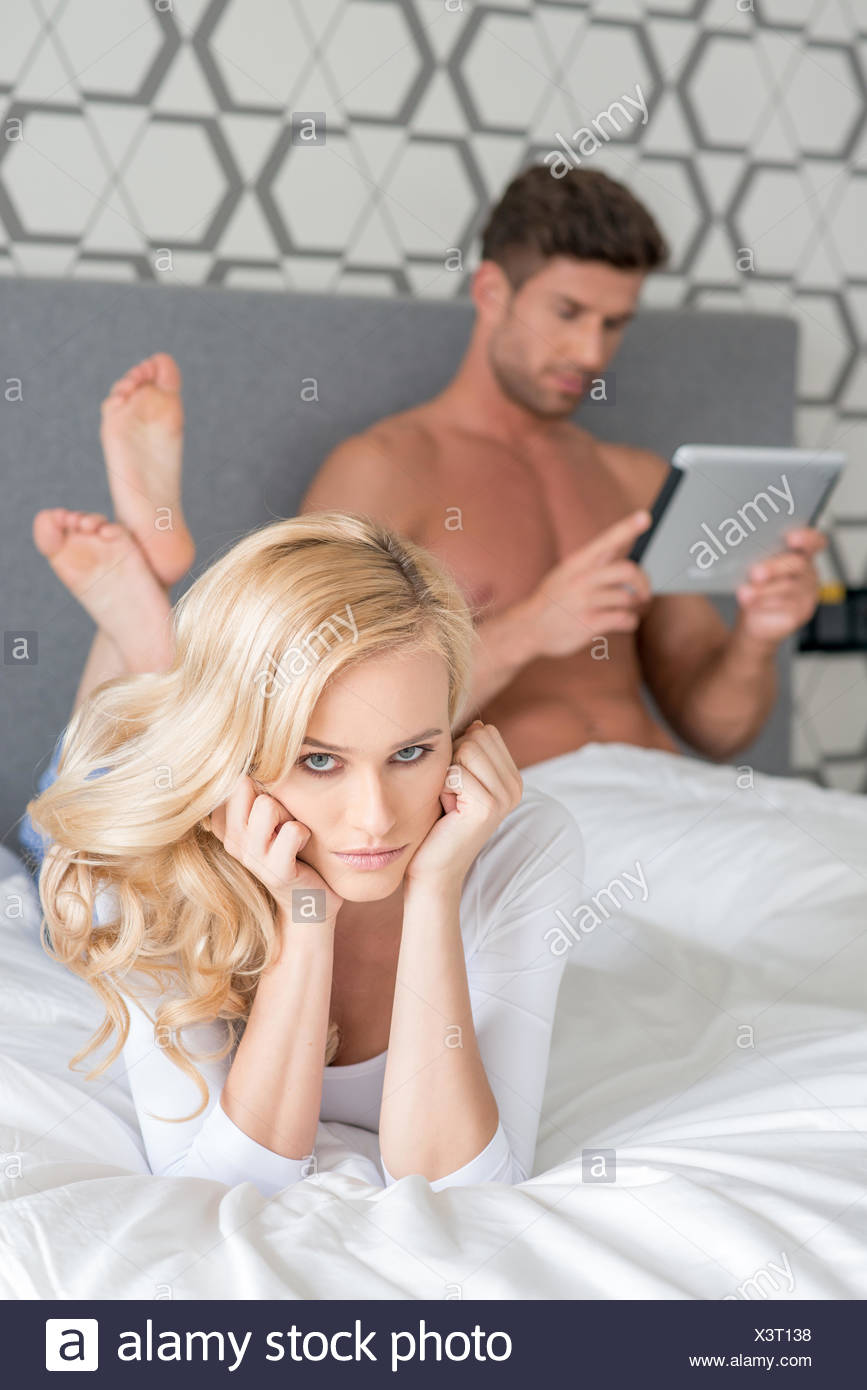 Disgruntled woman lying on her bed - Stock Image
