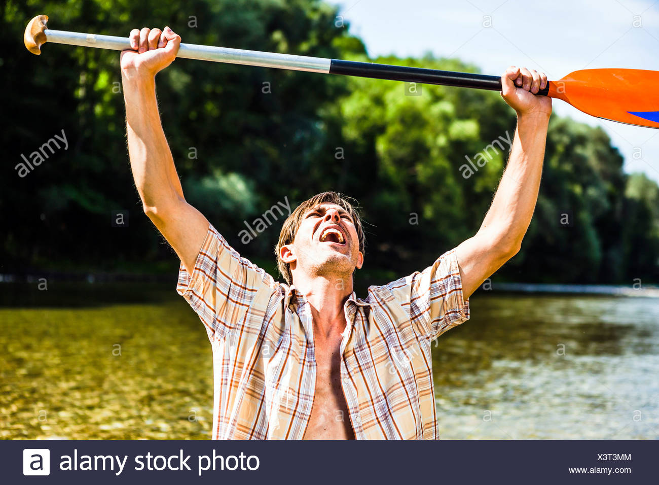 Young man cheering, a paddle in his hands, Bavaria, Germany - Stock Image
