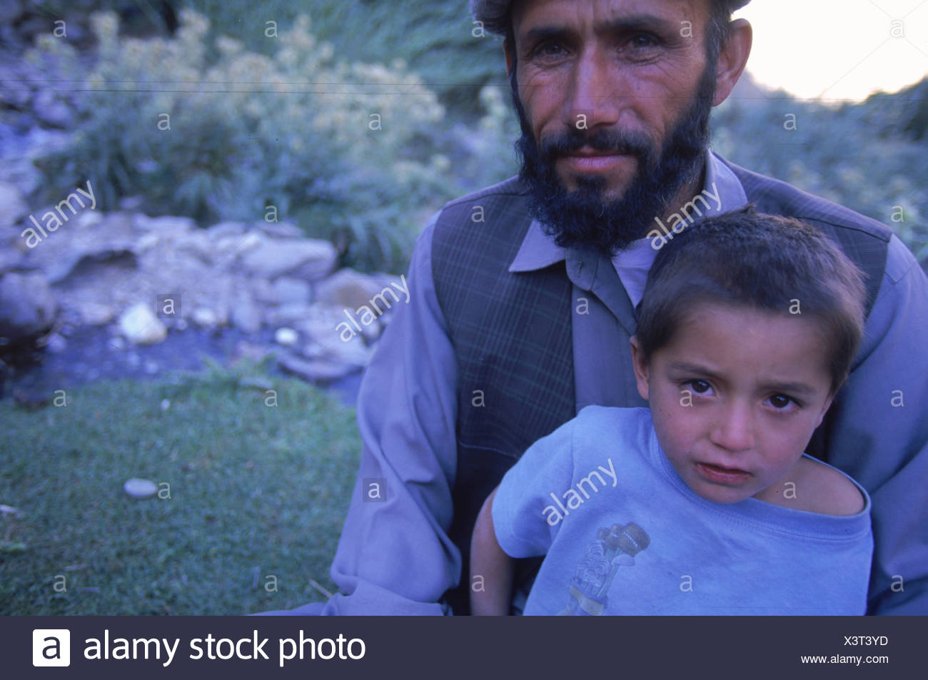 A Tajik man and his son relax in a field in the Panjshir Valley Hindu Kush mountains. - Stock Image