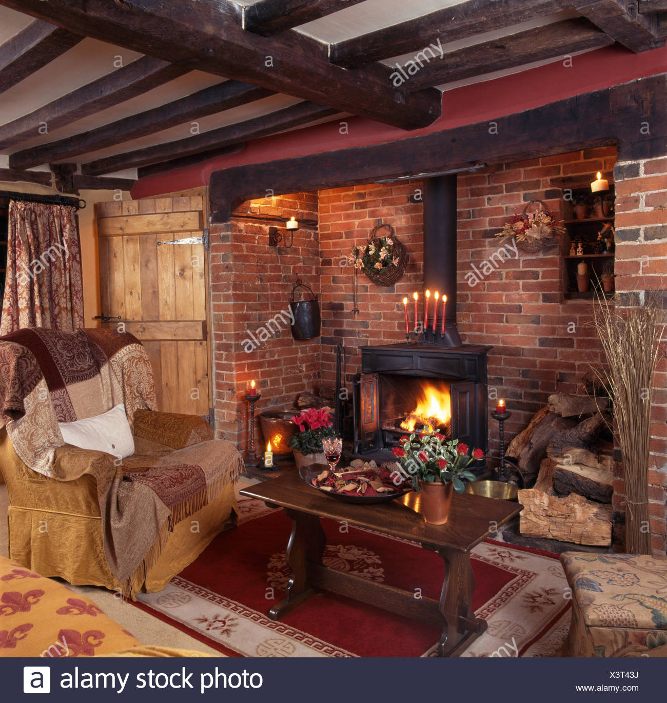 Wood burning stove in inglenook fireplace in  a beamed nineties country living room with an oak coffee table beside an armchair - Stock Image