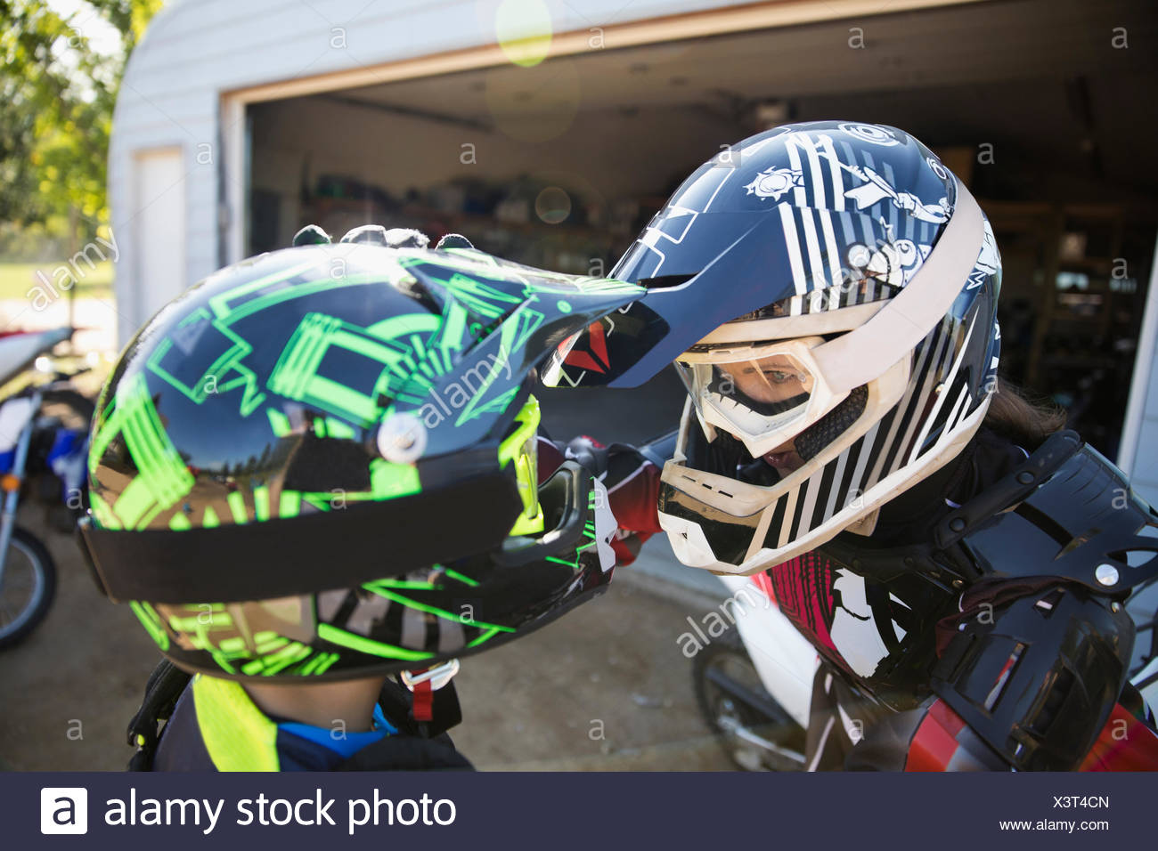 Mother and daughter face to face in motorbike helmets - Stock Image