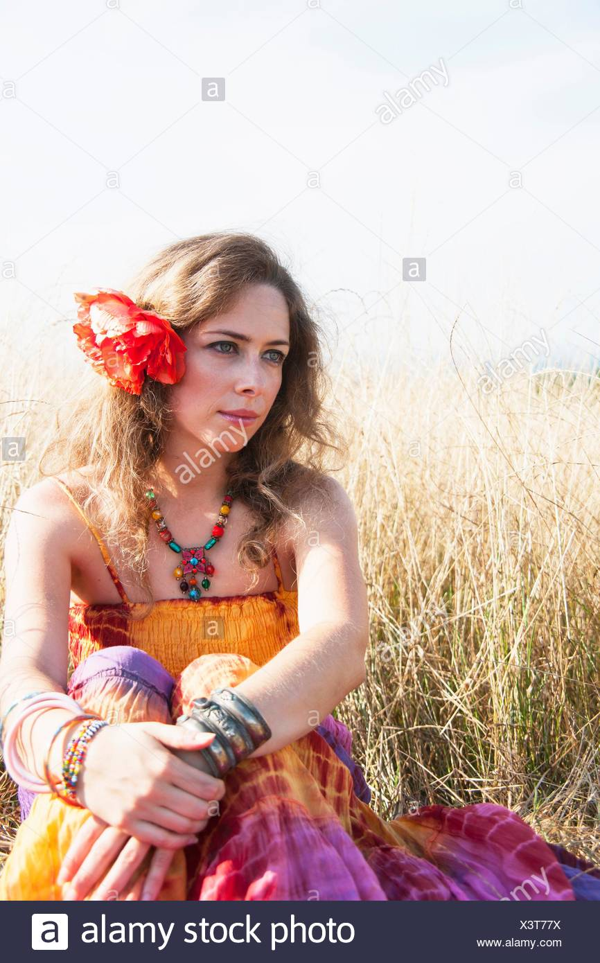 cee65b36 Portrait of mid adult woman, in hippy clothes, sitting in field - Stock  Image
