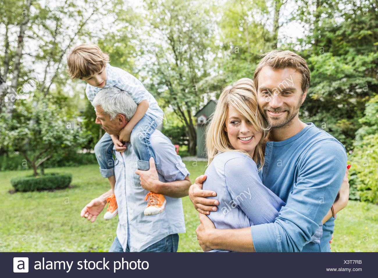 Mid adult couple hugging in garden - Stock Image