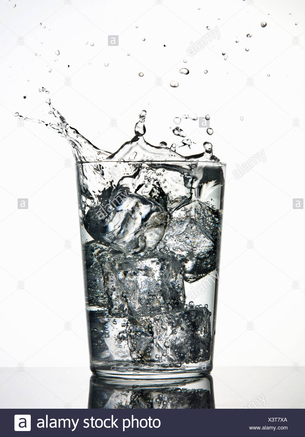 Ice cubes splashing into fizzy drink - Stock Image