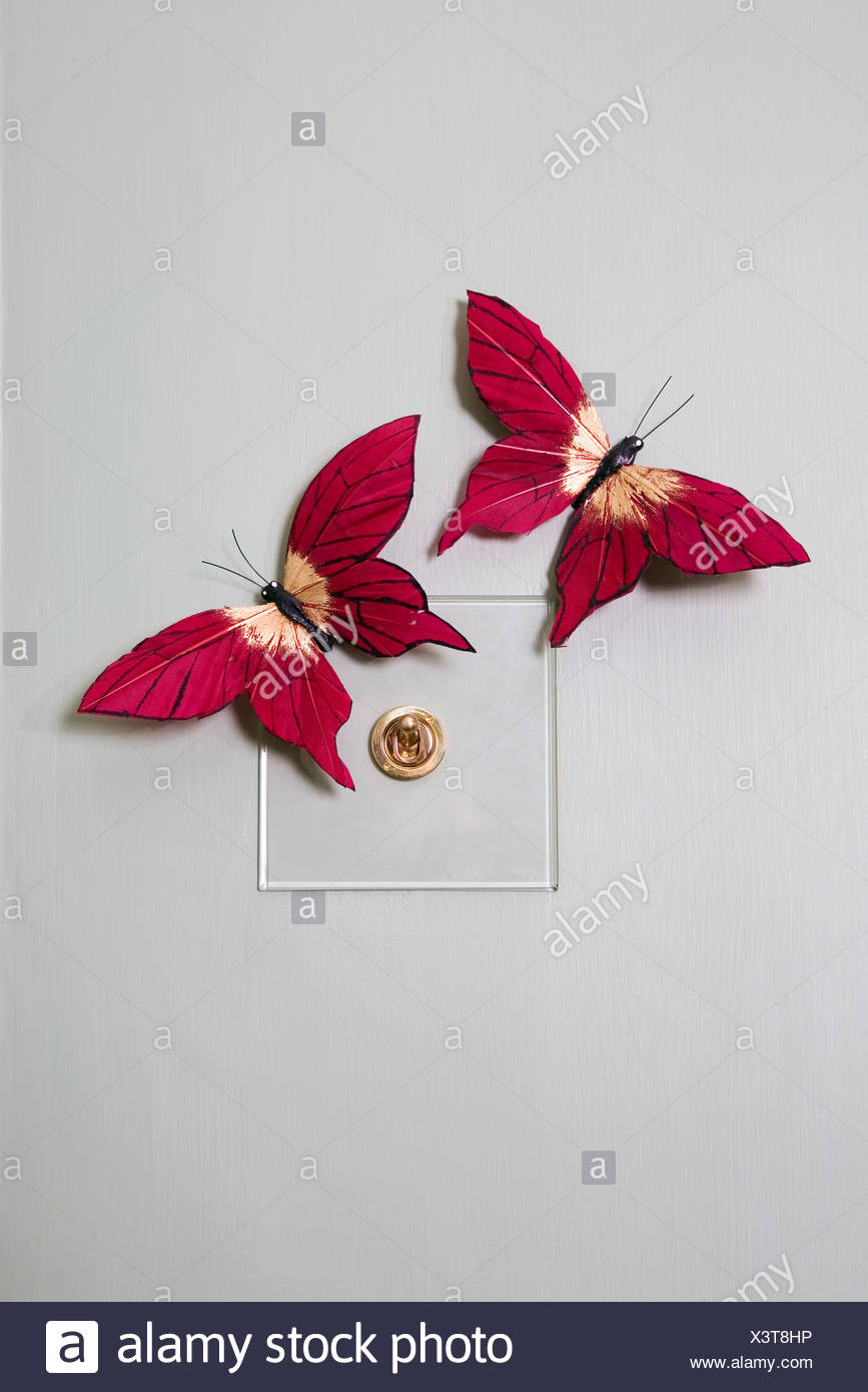 Fake butterflies on a lightswitch - Stock Image