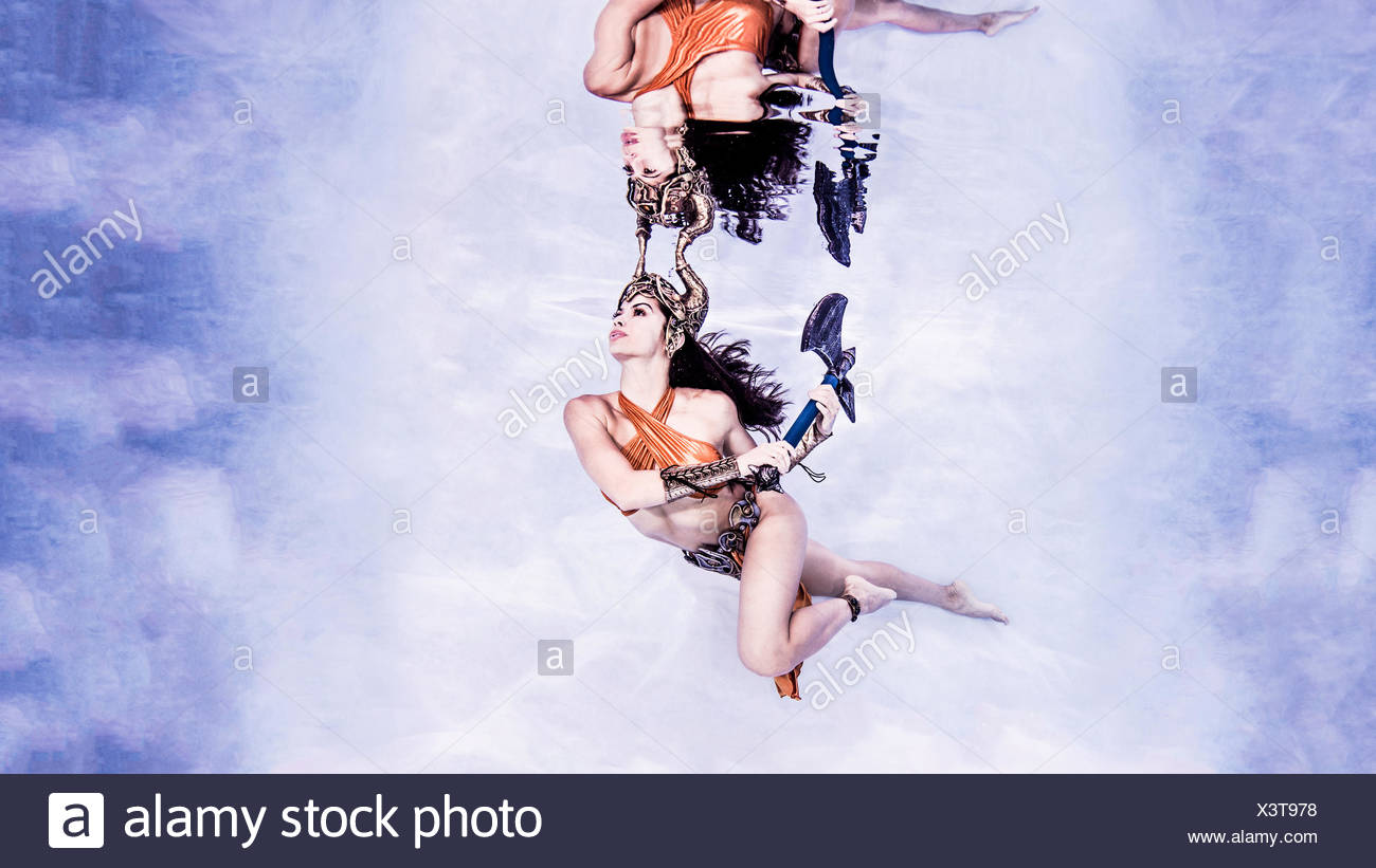 Woman wearing horned headdress holding axe underwater in swimming pool - Stock Image
