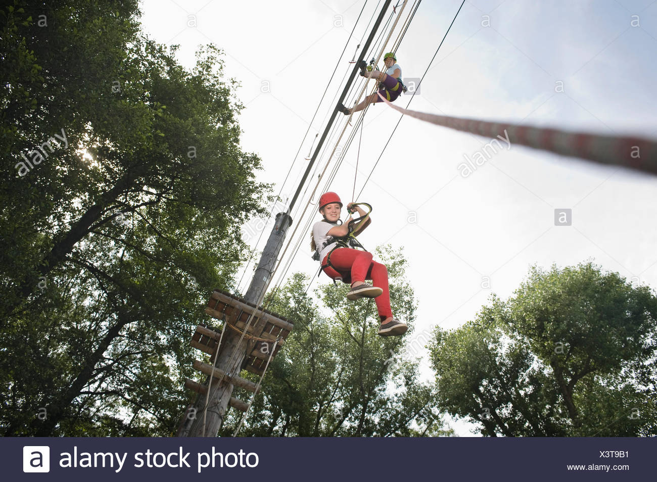 female teenager and a young female instructor in a climbing crag - Stock Image
