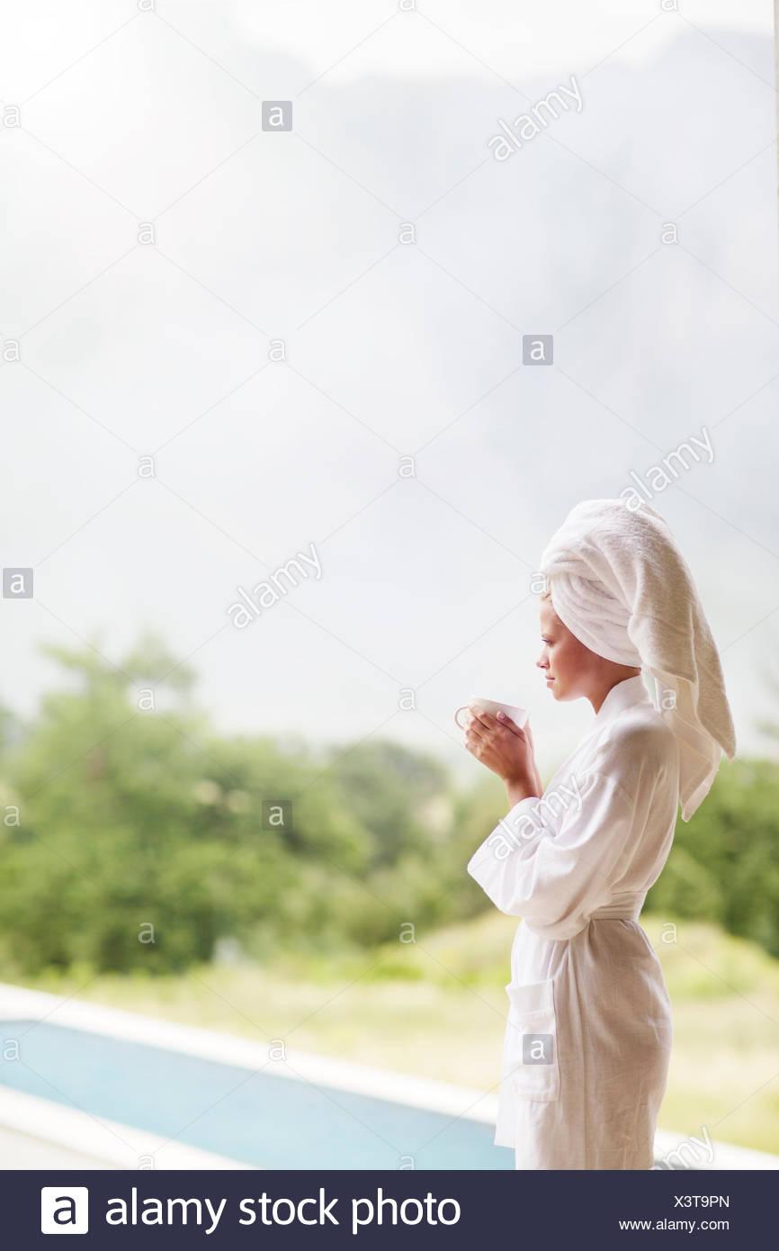 Woman in bathrobe drinking coffee outdoors Stock Photo