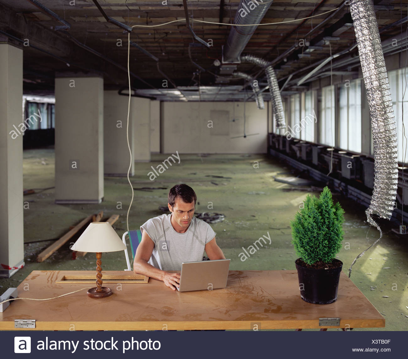 Man working alone in messy office - Stock Image