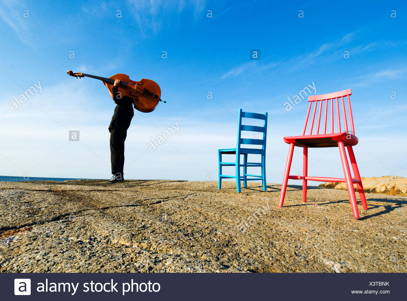 Jazz musician by two chairs carrying a contrabass on flat rock against blue sky and clouds - Stock Image