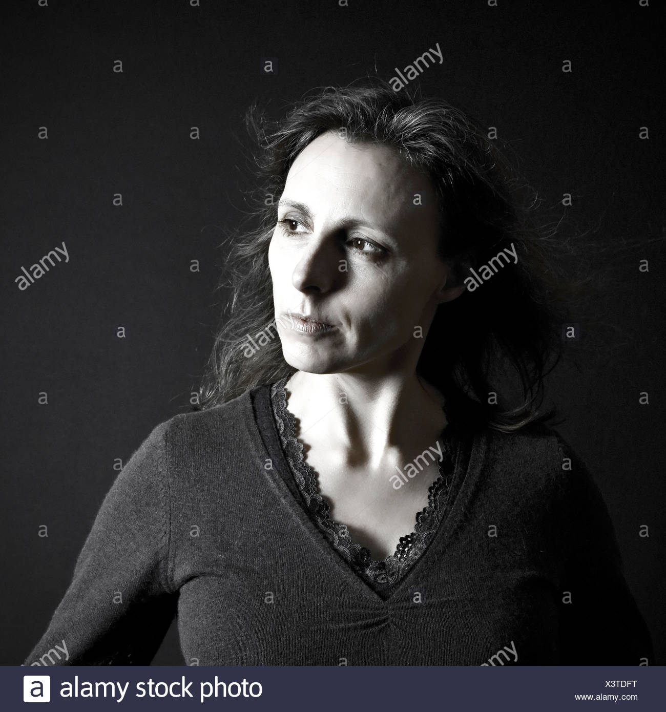 A thoughtful pose by a middle aged woman looking to the left - Stock Image