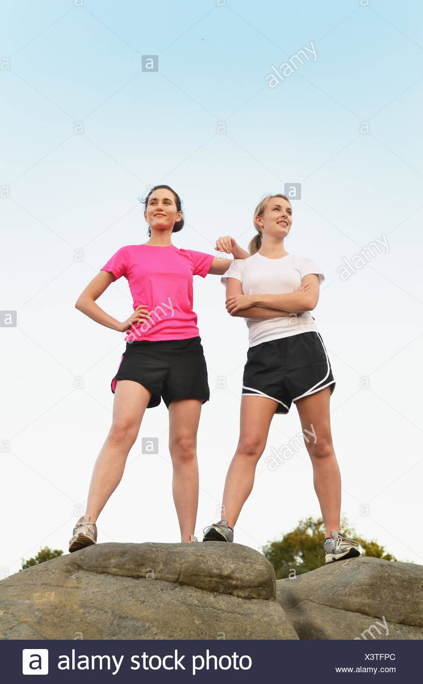 Portrait of two proud female runners on top of rock formation - Stock Image
